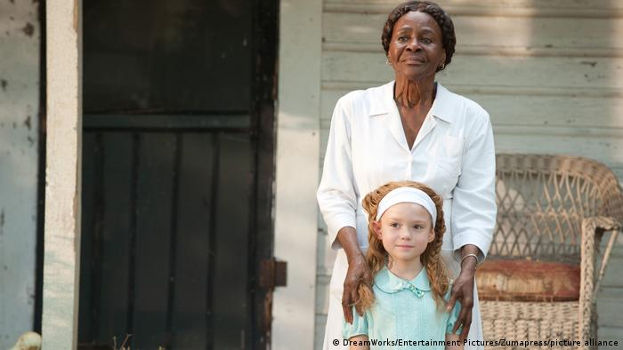 Film still from The Help. A woman has her hands on the should of a young girl. They stand on a porch