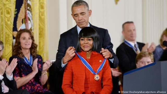 Barack Obama places a band with a medal around Cicely Tyson's neck, people look on and applaud