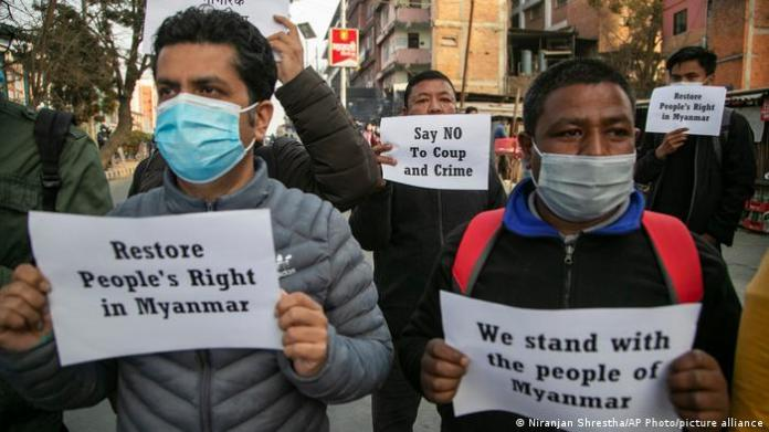 A small group of Nepalese Civil society activists hold placards reacting to the developments in Myanmar