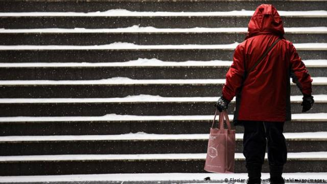 A woman stands by snow-covered stairs in Berlin