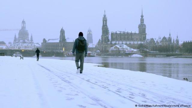 Pedestrians walk along the Elbe River in Dresden