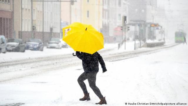 A woman with an umbrella crosses the road in Hanover, Lower Saxony