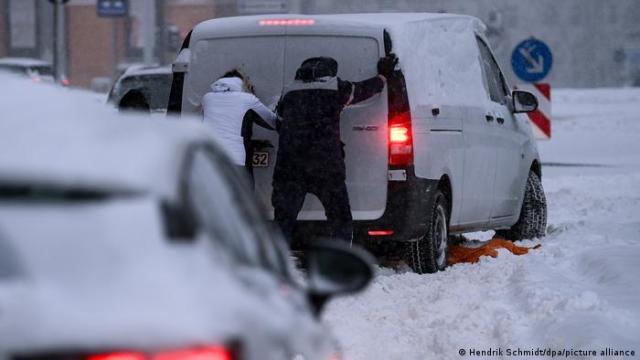People pushing stuck van in snow