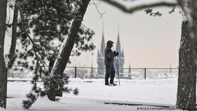 Man standing with sticks in snow in Prague