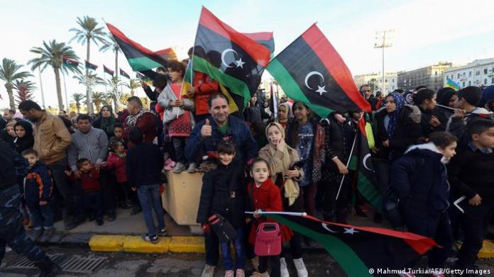 A Libyan family waves national flags in front of a celebrating crowd on the anniversary of the revolution.