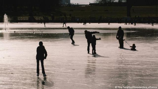 People walk and skate on a partially frozen pond in Cologne