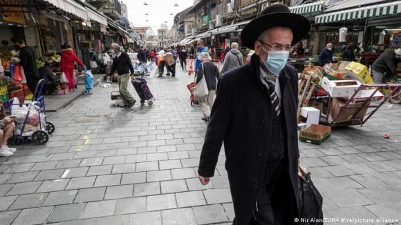 Shoppers at Jerusalem's Shuk Mahane Yehuda Market wear face masks