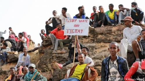 A group of refugees sit on the ground while one man holds a banner reading: 'Stop war on Tigray'