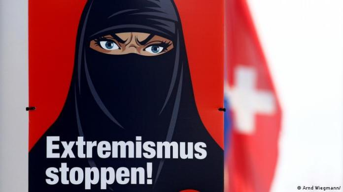 A Swiss national flag flies behind a poster against wearing the burqa. It features a scowling caricatured woman's face with veil and has the text Stop extremism!