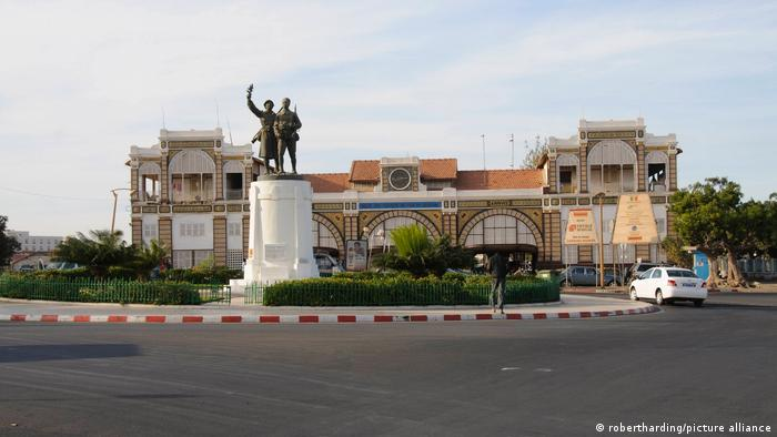Outside view of train station in Dakar, with low-rise building and colonial statue in front