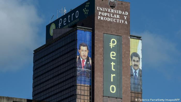 The logo of the Petro is displayed next to images of Venezuelan late President Hugo Chavez and Venezuelan President Nicolas Maduro in a building in downtown Caracas
