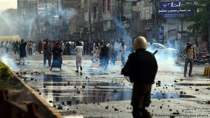 Pakistani police use teargas and water cannon against anti-France Islamist protesters during a protest in Lahore