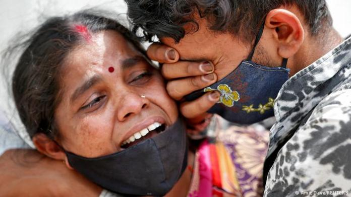 A woman mourns with her son after her husband died due to the coronavirus