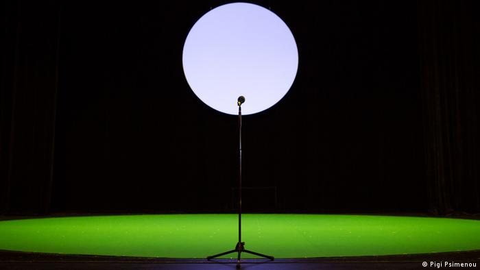 An empty stage with the moon and a microphone.