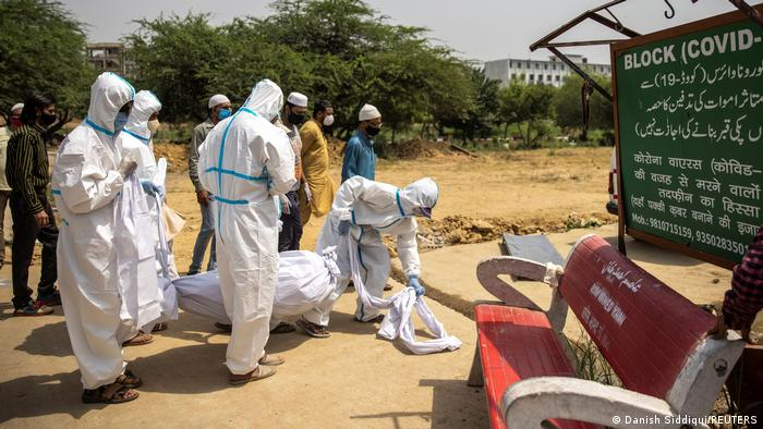 Health workers carry a body.