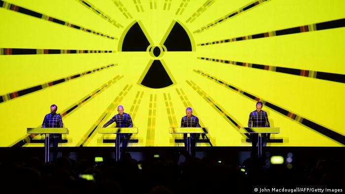 4-piece band perform on synthesizers in front of a projected radioactivity szmbol