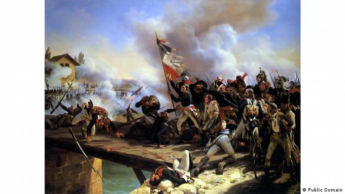 Napoleon in a painting showing him carrying a flag amid a battle on a bridge.