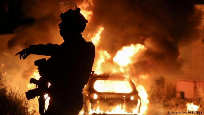 An Israeli policeman gestures as a car burns.