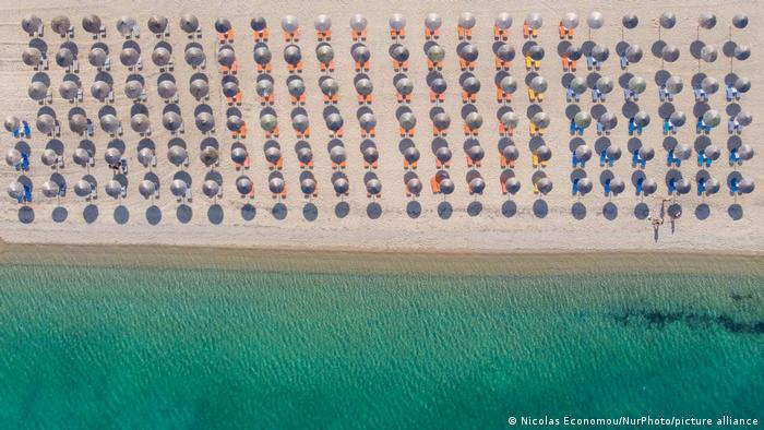 Bird's view of a beach in Halkidi with lines of sun shades but without any people.