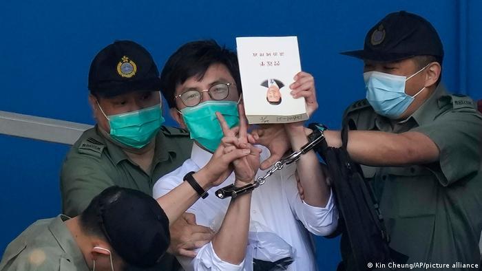 Polizisten führen den Hongkong Pro-Demokratie-Aktivist Avery Ng ab, der ein Buch mit dem Porträt von Chinas Präsidenten Xi Jinping in der Hand hält