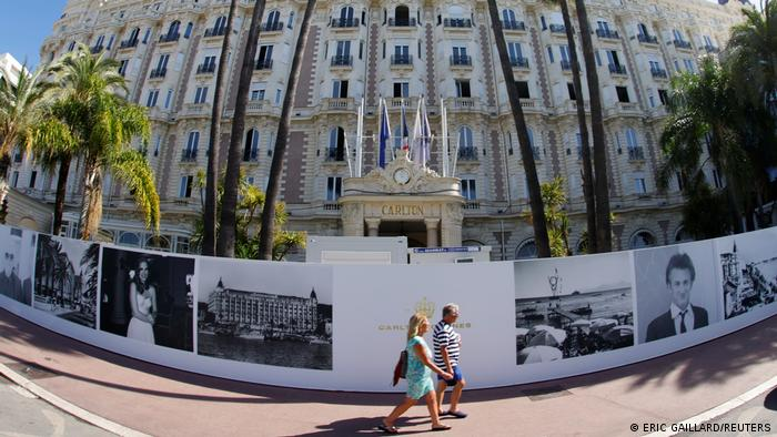 People walk past the Carlton hotel in Cannes as the French Riviera prepares for the 2021 edition of the Cannes Film Festival.