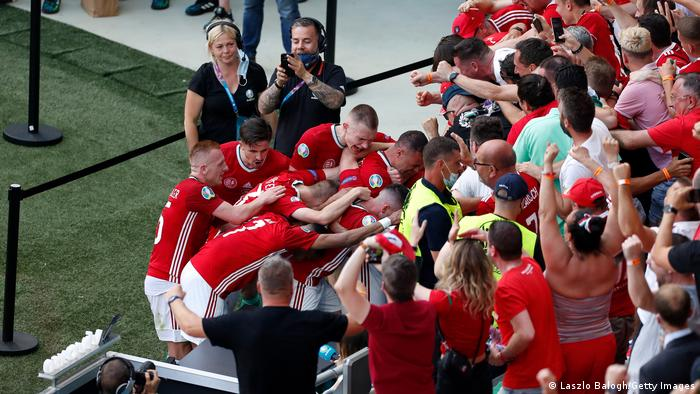 Attila Fiola celebrates with Hungary fans after scoring the opener