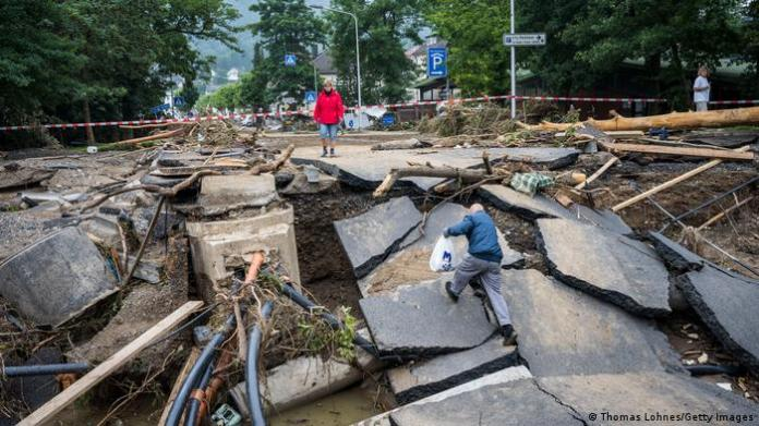 An old man climbs over a destroyed bridge to his neighborhood in Bad Neuenahr, Germany