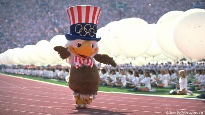 Huge eagle figure with a hat and bow tie dances down a race track, many women wearing white sit in the abkground
