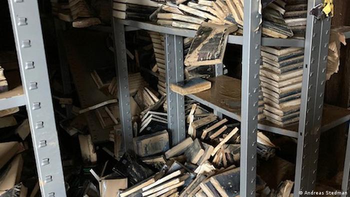 Books lying in disarray on metal bookshelves
