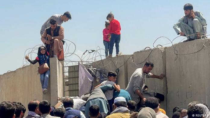 Children stand on top of a concrete wall as desperate crowds clamber into the Hamid Karzai International Airport precinct.