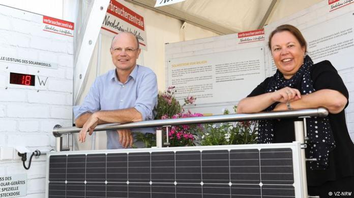 A man and a woman leaning on a solar panel system