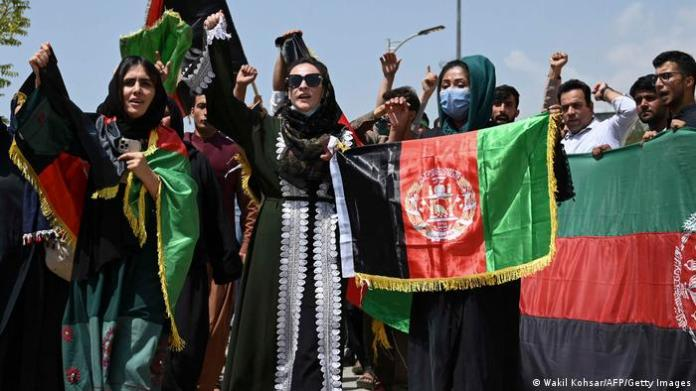Afghans in Kabul holding up their national flag in the street