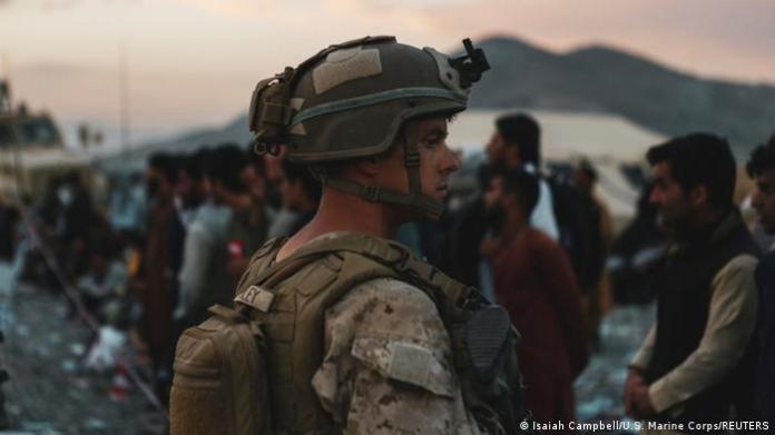 A marine assists evacuees at Kabul airport