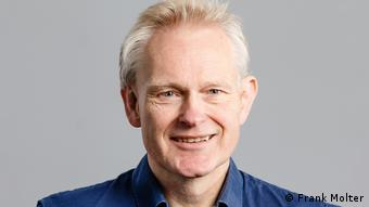 A portrait of Wolfgang Günther in a blue shirt.