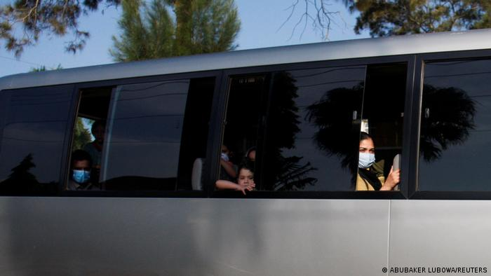 Afghan refugees sitting on a bus leaving Uganda's Entebbe airport