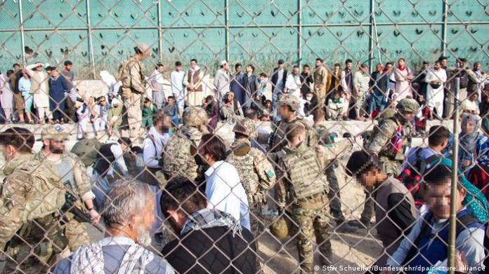 Soldiers and civilians in a crowd at Kabul airport
