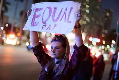 "A woman holds a sign that reads, ""Equal Pay"" during ""A Day Without A Woman"" demonstration on March 8, 2017 in Miami."