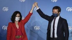 Conservative Madrid regional president Isabel Diaz Ayuso, left, and Popular party leader Pablo Casasdo wave outside the popular party headquarters in Madrid, Spain.