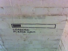 grafitti on a white wall saying 'loading, please wait...'