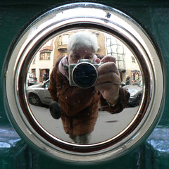 Image of a photographer's reflection in a doorknob.
