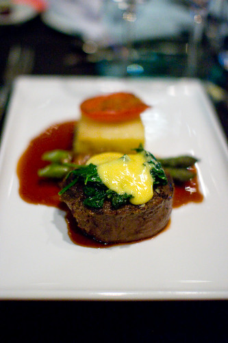 Beef fillet with wilted greens, pancetta wrapped asparagus and potato gratin stack