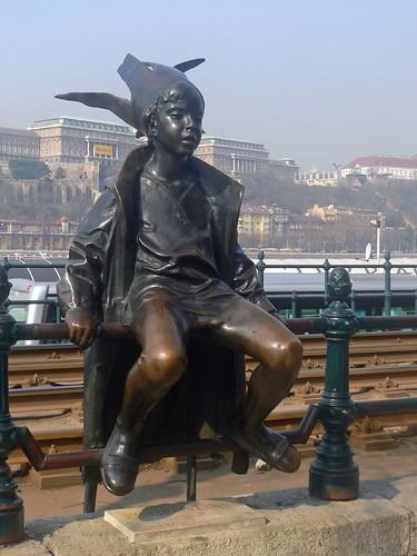 Kiskiralylany, a bronze elf, sitting on the Pest side of Budapest