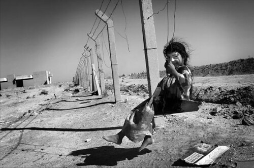 child on a swing made from barbed wire Southern Iraq, 2004