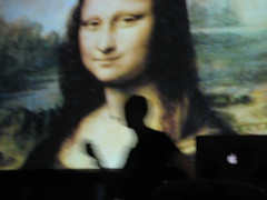 Ben Hammersley dancing around the stage flanked by Mona Lisa and a battered PowerBook