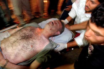 Palestinians rush victim to Al Shifa Hospital after F16 attack Jul 12 2006.jpg