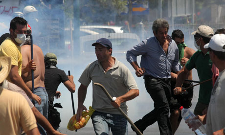 Taxi drivers run from teargas during clashes on the island of Crete, Greece. Photograph -- Image Photo Services - AP