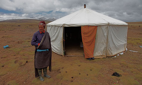 Tibetan nomad  Phuntsok Dorje outside his tent on grasslands turning to desert, Tibet