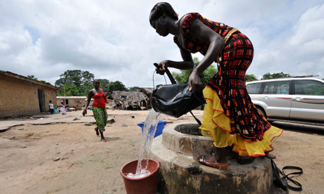MDG : Access to water  : A woman draws water from a water well