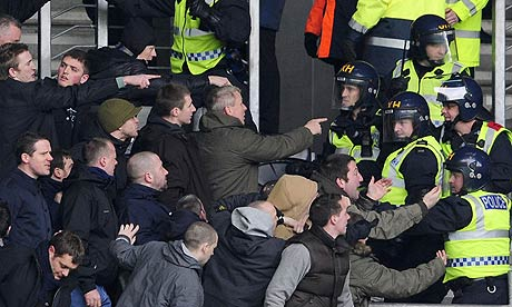 Millwall fans in their natural environment, surrounded by cops in riot gear.