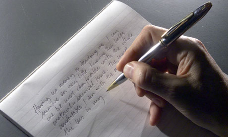 A hand writing with a pen on paper